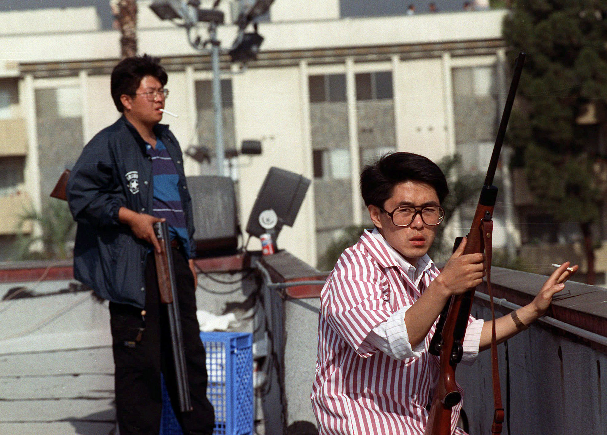 ** ADVANCE FOR FRIDAY, APRIL 26 AND THEREAFTER--FILE ** Two Korean men stand on the roof of a grocery store with rifles to prevent looters from entering the store in this file photo taken April 30, 1992, in Los Angeles. On April 29, 1992, four white police officers were declared innocent in the beating of black motorist Rodney King, and Los Angeles erupted in the deadliest riots of the century. Three days later, 55 people were dead and more than 2,000 injured. Fires and looting had destroyed $1 billionworth of property. (AP Photo/John Gaps III)
