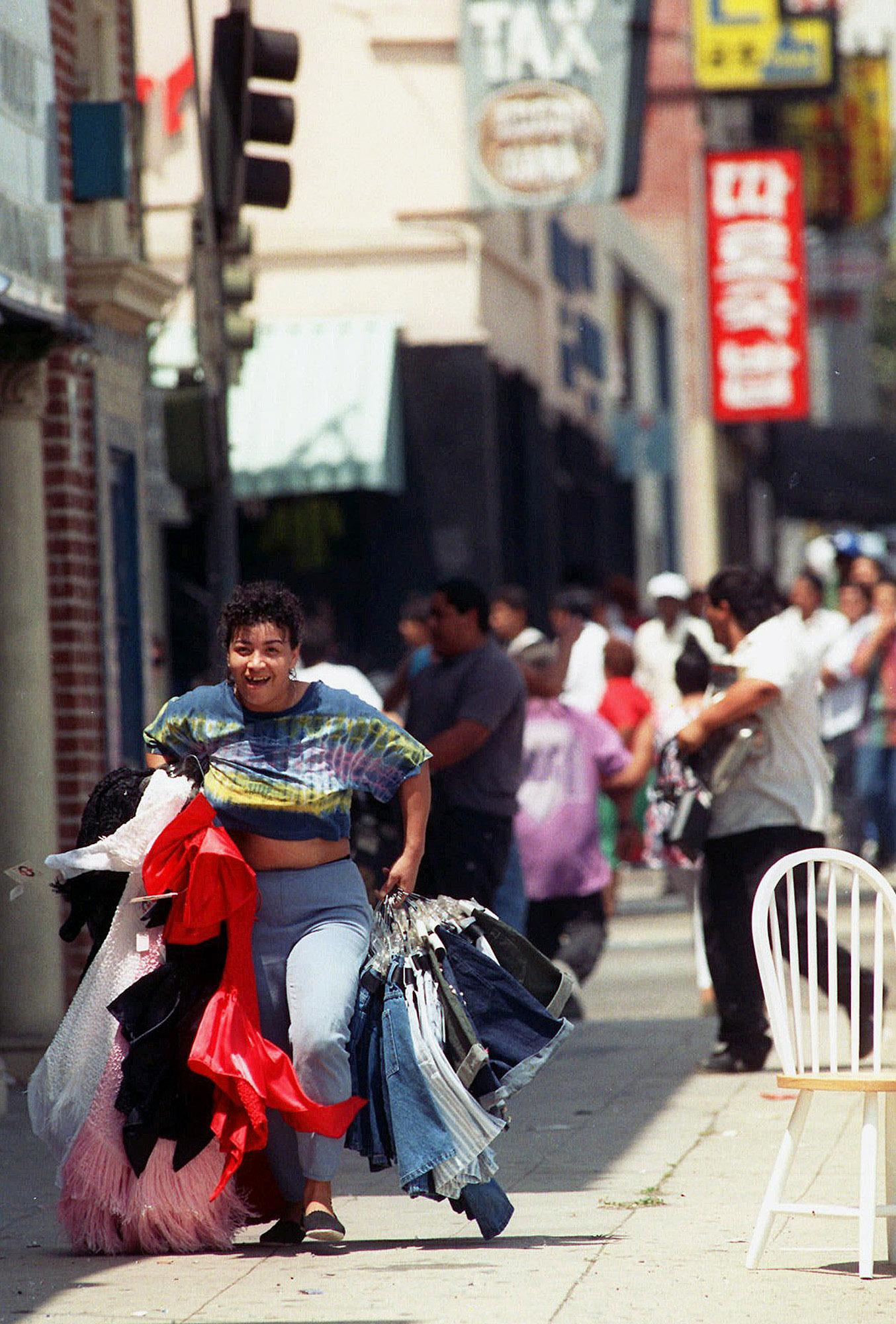 ** ADVANCE FOR FRIDAY, APRIL 26 AND THEREAFTER--FILE ** An unidentified woman sprints down Vermont Ave. with looted clothing in this file photo taken May 1, 1992, in South central Los Angeles. On April 29, 1992, four white police officers were declared innocent in the beating of black motorist Rodney King, and Los Angeles erupted in the deadliest riots of the century. Three days later, 55 people were dead and more than 2,000 injured. Fires and looting had destroyed $1 billion worth of property. (AP Photo/Bob Galbraith)