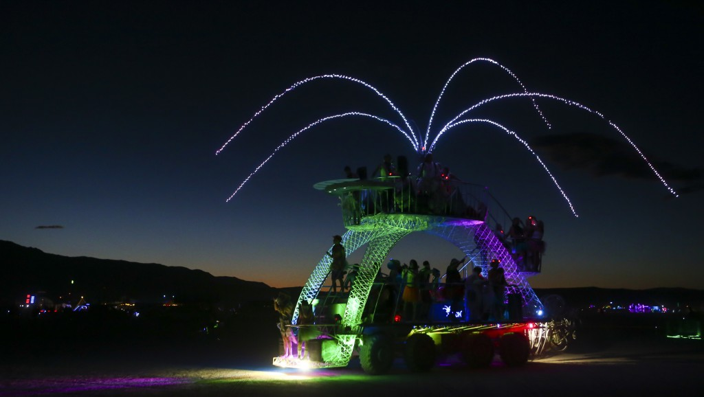 In this Tuesday, Aug. 30, 2016 photo, people dance in a moving art car during Burning Man at the Black Rock Desert near Gerlach, Nev. (Chase Stevens/Las Vegas Review-Journal via AP)