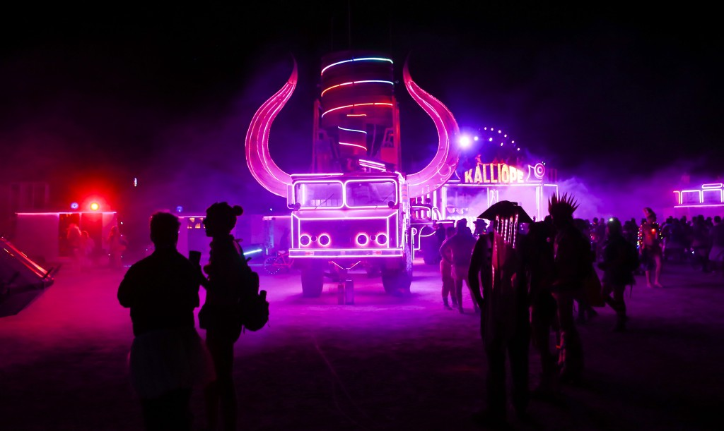 In this Tuesday, Aug. 30, 2016 photo, attendees walk by art cars during Burning Man at the Black Rock Desert near Gerlach, Nev. (Chase Stevens/Las Vegas Review-Journal via AP)