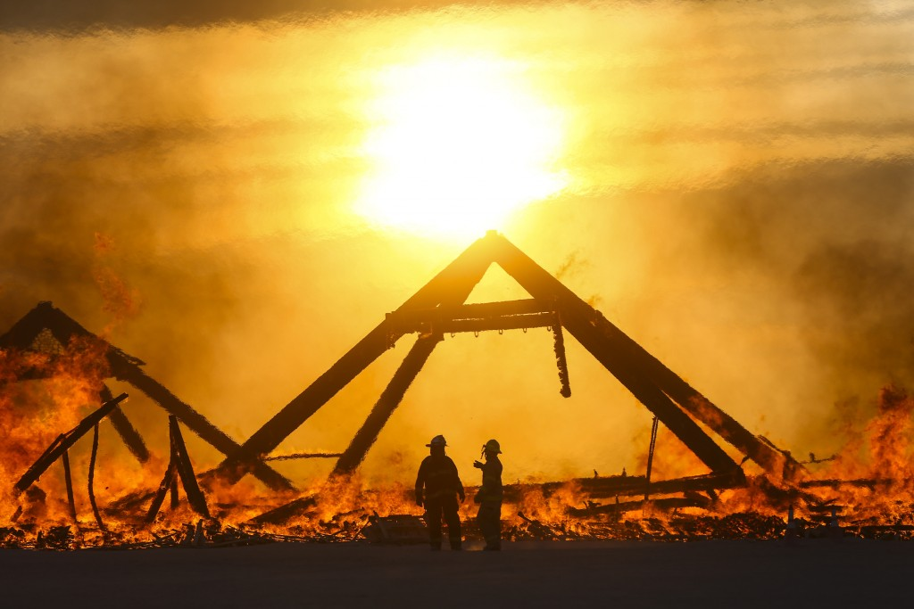 "In this Friday, Sept. 2, 2016 photo, ""Catacomb of Veils"" art installation burns at sunrise during Burning Man at the Black Rock Desert of Gerlach, Nev., north of Reno. (Chase Stevens/Las Vegas Review-Journal via AP)"