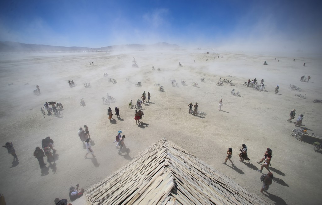 Attendees approach the Catacomb of Veils art installation as dust kicks up along the playa during Burning Man at the Black Rock Desert north of Reno, Nev., Thursday, Sept. 1, 2016. (Chase Stevens/Las Vegas Review-Journal via AP)